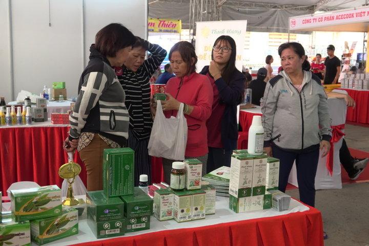 Người dân tham khảo và mua sản phẩm thảo dược trong ngày hội